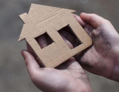 Homeless boy holding a cardboard house, dirty hand