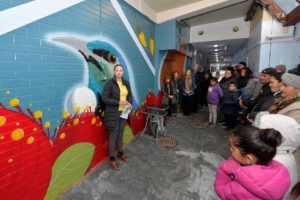 Mel Gardner presenting to the young people, who helped paint the mural, and their families at the Queens Arcade mural launch