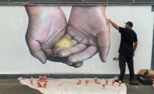 Well known artict Mr G finishing the 'He kakano ahau ahau - I am a seed' mural on the Wellington Electrical substation in Wainuiomata