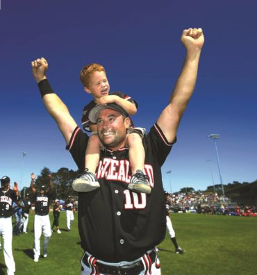 Rhys and son Danny doing a lap of honour after New Zealand won the softball World Series in 2013