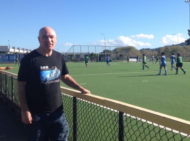 Steve McCarthy next to the hockey turf