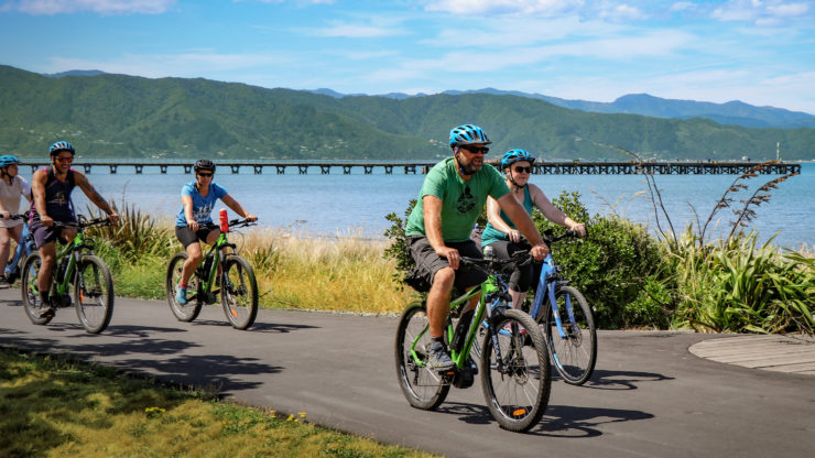 Cycling along Petone Esplanade beach group in front of wharf