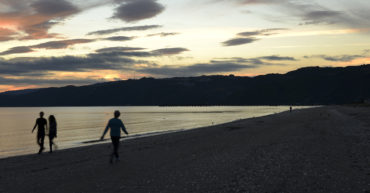 People walking along Petone Beach at sunset
