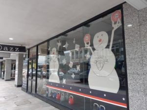 Window display of two snowmen working out.