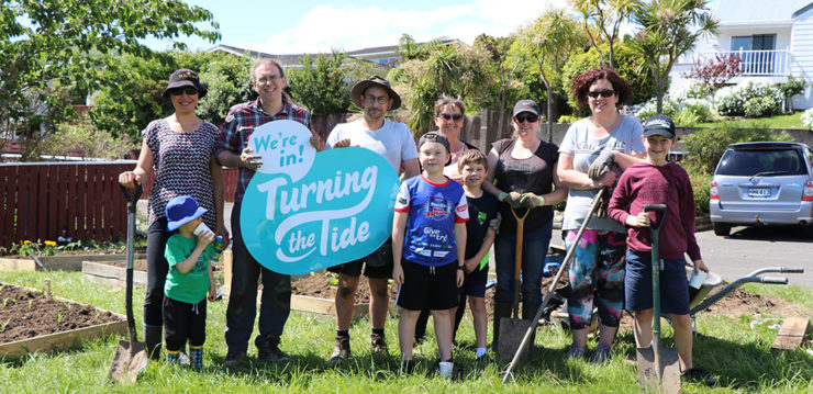 People in Garden holding a turning the tide sign