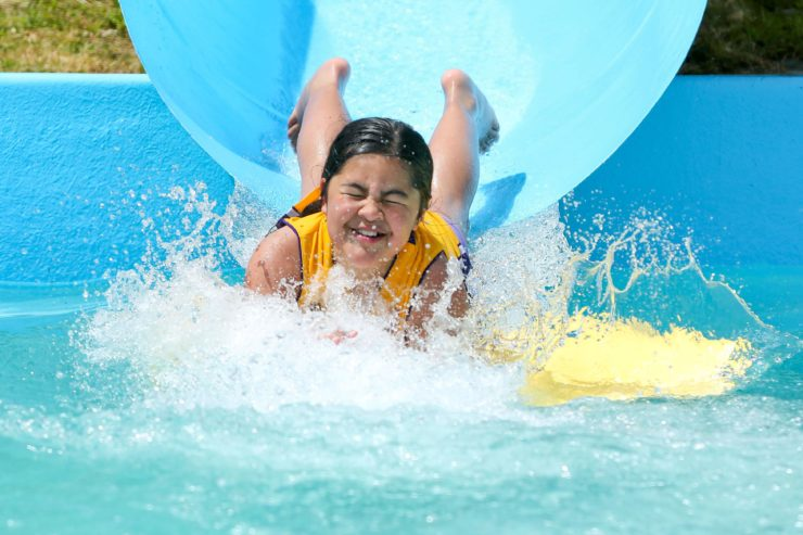Child coming out of water slide at a Summer Pool