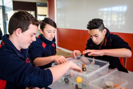 Three young men doing Science experiments in the classroom