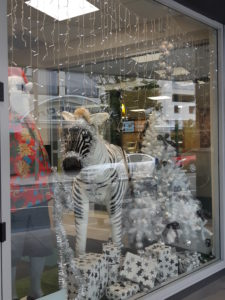 A window display of a summery santa and a tinsel covered zebra