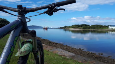 Handlebars of a bike overlooking a body of water
