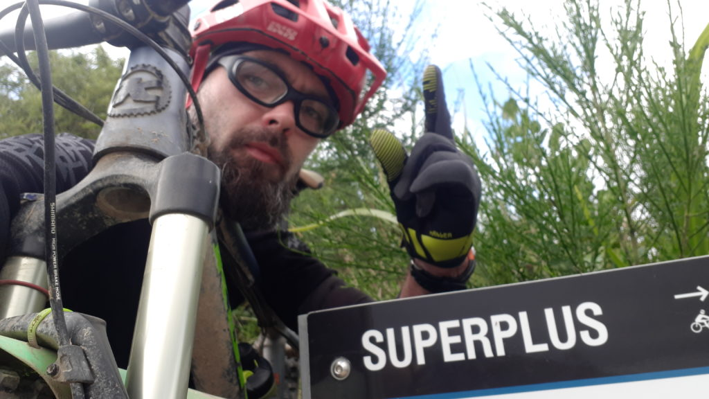 Shane next to the Superplus sign. Super Plus is a fast down hill trail from the top of the Wainuiomata hill into Lower Hutt.