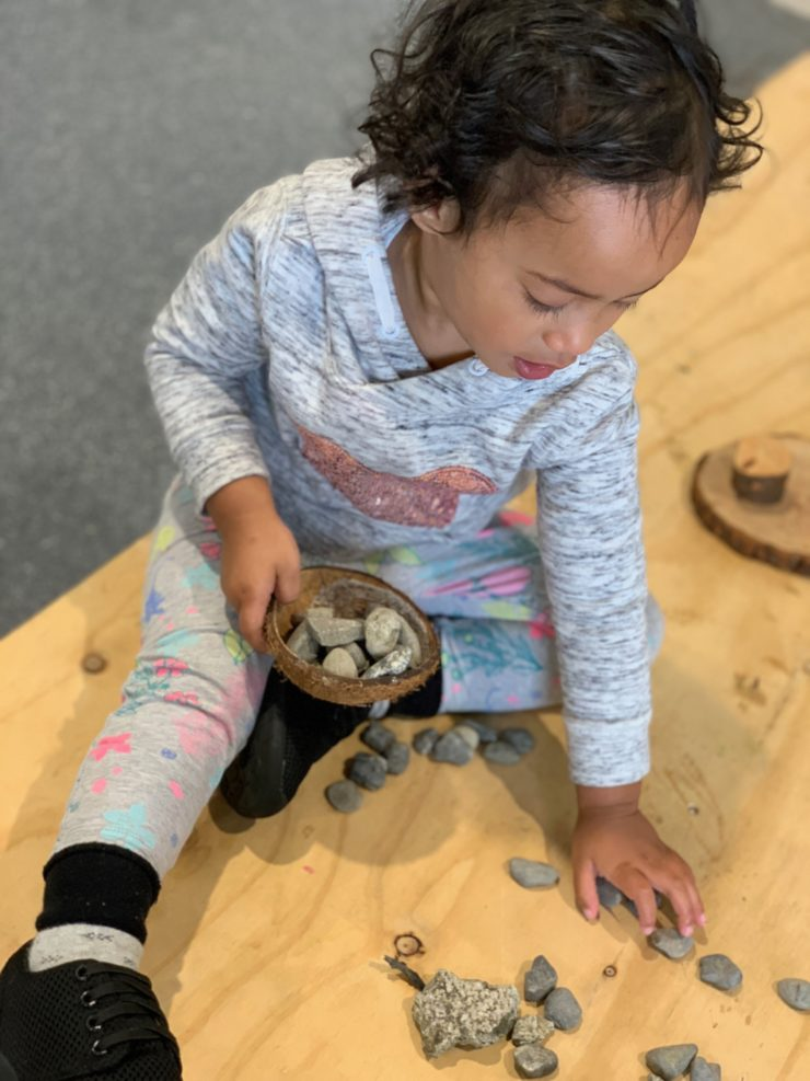 A child playing with stones during the Pasifika Poly Playgroup at Koraunui Stokes Valley Community Hub