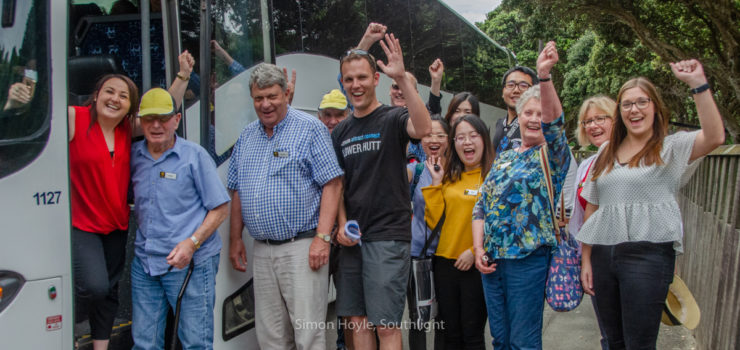 Tour group about to board a bus, looking happy and waving