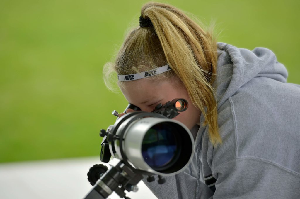 Young lady looking through a telescope