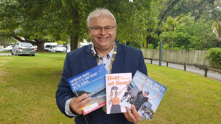 Mayor Ray Wallace smiling and holding two ward books and a Hutt@Heart magazine