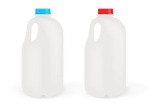 Two milk bottles, one with a blue lid, one with a red lid.