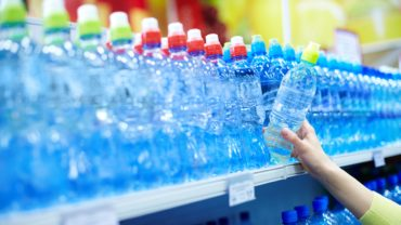 Close-up of choosing mineral water in a shop