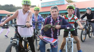 RIDE Holidays' Karl Woolcott with children riding the new bikes at Taita Central School.
