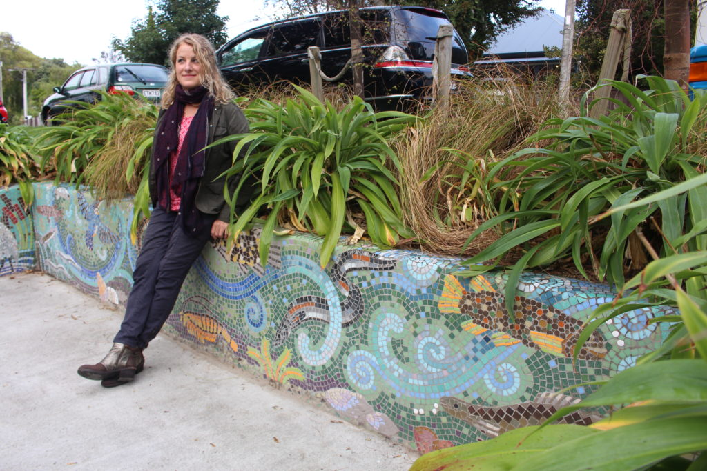 Artist Rachel Silver leans against the new mural