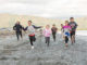 Young people running on the beach.