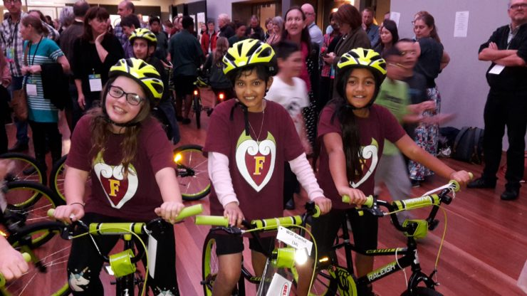 Three school students looking happy stting on bikes.
