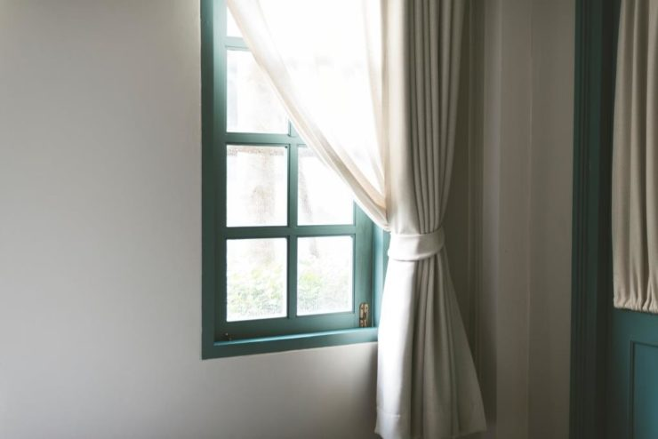 Simple wooden window with white curtain