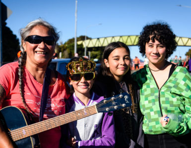 Woman with guitar and three young people standing in front of Pukeatua Bridge.