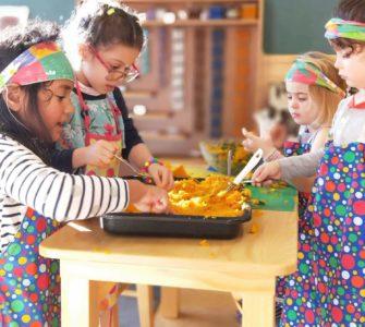 Wā Ora Montessori students mashing pumpkins for pumpkin soup