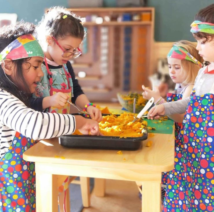 Wā Ora Montessori students mashing pumpkins for pumpkin soup