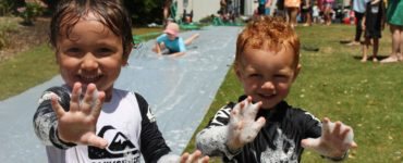 Tamariki enjoying the bubbles and slip 'n' slide at Riddiford Gardens Play Day