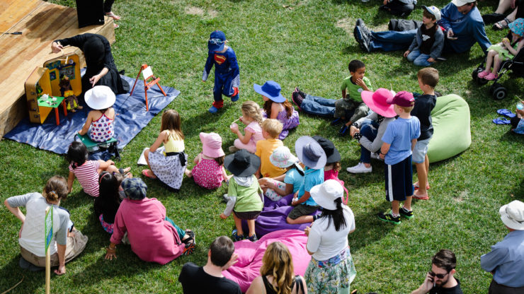 Children and families sitting on a lawn, watching a performance