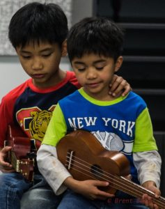 Two boys play the guitar