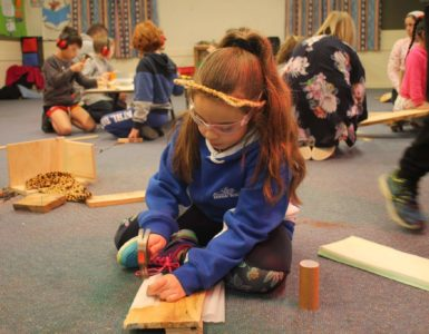 young girl hammering nails into a wood plank