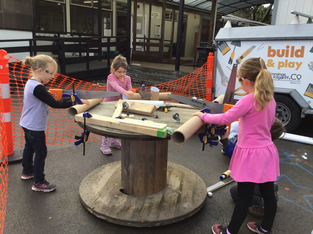 children use saws to cut large cardboard tubes
