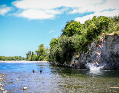 Young person jumping from Taita Rock into the Hutt River