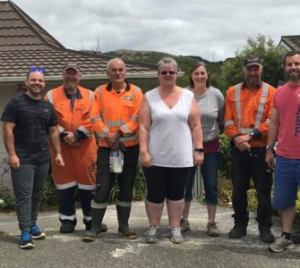The Hutt City Council Parks and Gardens Team and DownerNZ stand outside a house with shovels - they look happy.