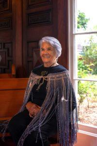 Matekino Lawless, an elderly Māori woman sits by a window wearing a woven kākahu (cloak)