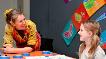 Tutor and child smile at each other during an art workshop.