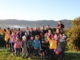 Children and parents from Belmont School stand in the morning sun in front of a view of the valley of Lower Hutt.