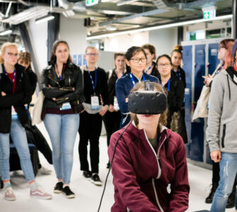 Young woman sits in VR headset as group behind watches