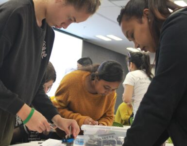 Three female youth work on building a robot