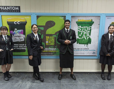 Taita Rangatahi stand in front of their posters for Hutt City Council' rubbish and recycling campaign