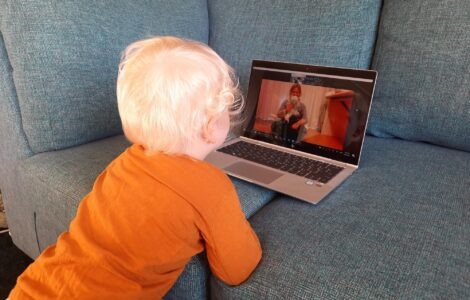 Toddler watches a presenter on a screen
